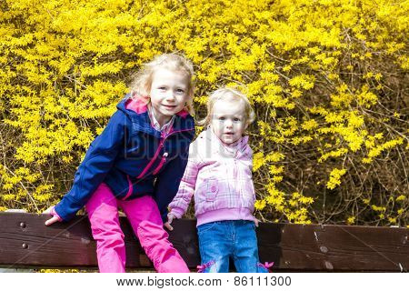 two little girls sitting on bench in spring