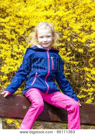 little girl sitting on bench in spring