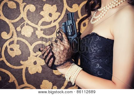 Woman Wearing Black Corset And Pearls And Holding A Gun Against Retro Background
