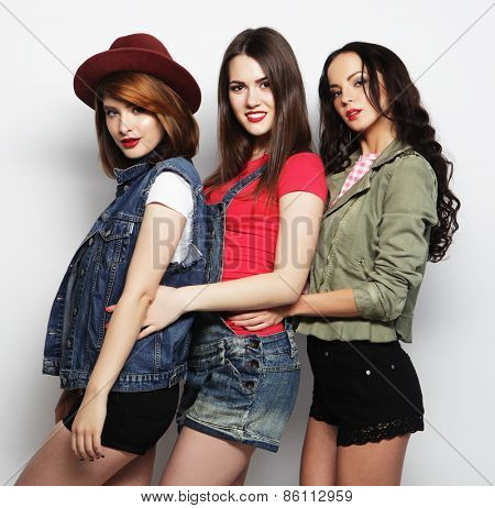 Three stylish sexy hipster girls best friends.Standing together and having fun. Looking at camera. Over gray background.