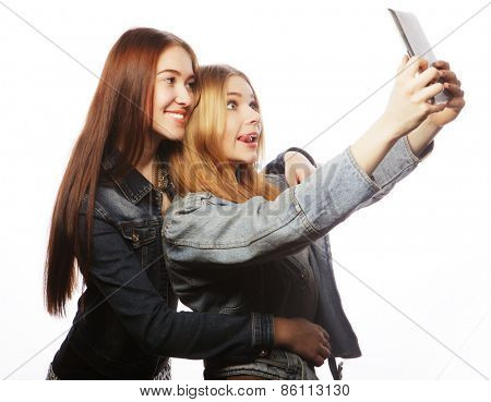 Two pretty young women taking a self portrait with a tablet, isolated on white
