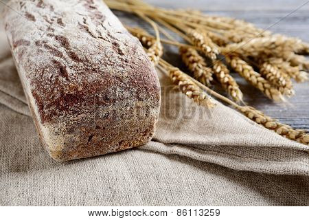 Fresh Loaf Of Bread With Wheat Spikelets On A Sacking