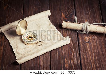 Old Unrolled Map, Rolled Map And Compass On Wooden Table