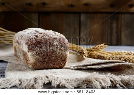 Fresh Black Bread With Wheat Spikelets On A Wooden Background
