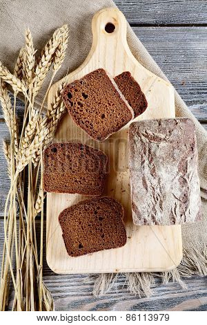 Slices Of Rye Bread With Spikelets Of Wheat On A Cutting Board