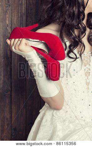 Bride Holding A Pair Of Red Shoes Against Wooden Background