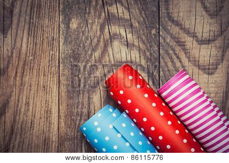 Rolls Of Colored Wrapping Paper On Wooden Background