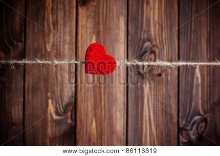 Red Fabric Heart Hanging On Clothesline Against Wooden Background