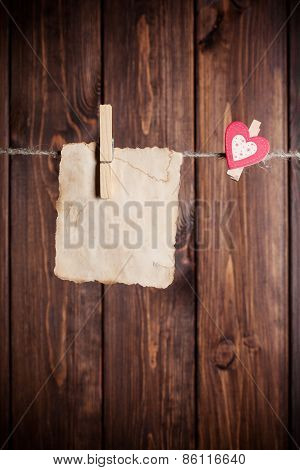 Old Paper Sheet And Small Paper Heart Hanging On Clothesline Against Wooden Background