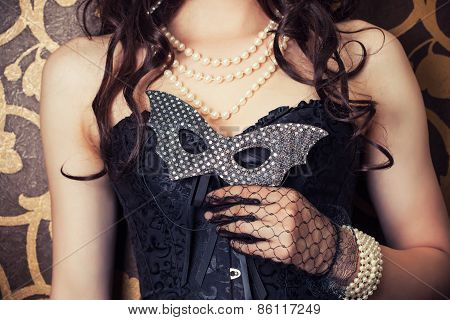 Woman Wearing Black Corset And Pearls And Holding A Carnival Mask Against Retro Background