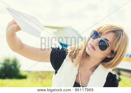 Beautiful Woman Holding Paper Plane Against Real Plane