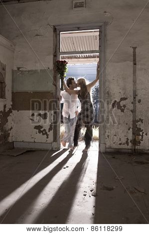 Silhouette and shadows of young attractive couple in old doorway