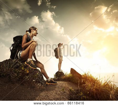 Two young tourists with backpacks relaxing on rocks and enjoying sunset