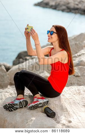 Sport woman on the rocky beach