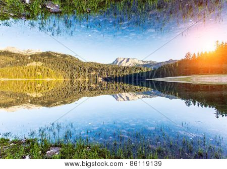 Black lake in Durmitor national park in Montenegro, Balkans, Europe. Dramatic scenery. Beauty world. Flip canvas vertical. Double exposure effect.