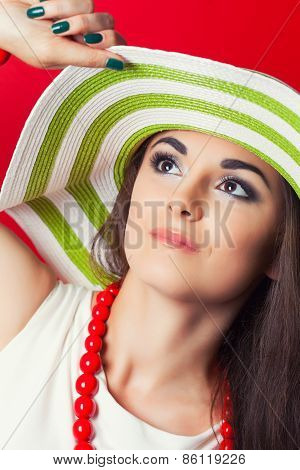 Beautiful Young Woman Wearing Striped Hat Against Red Background