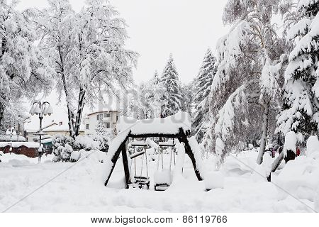 Wooden Children's Swing Covered By Snow