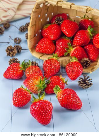 Basket With Strawberries And Fir Cones Spilling On A Table