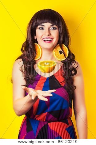 Beautiful Young Woman Wearing Earrings Made From Orange And Throwing Up An Orange Half Against Yello