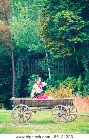 Beautiful Young Woman Wearing National Ukrainian Clothes Sitting On Old Horse Drawn Wooden Cart