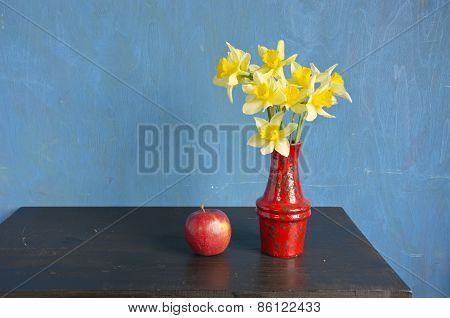Yellow Fresh Spring Narcissus In Red Vase. Beautiful Still Life