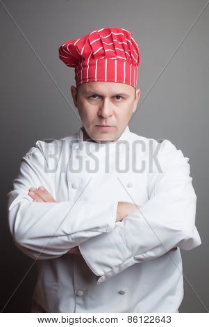 Professional chef with red hat, studio shot over gray background