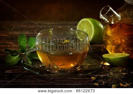 Tea In A Glass Teapot And A Transparent Cup With Lime And Mint