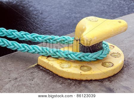 Yellow Mooring Bollard With Green Ropes