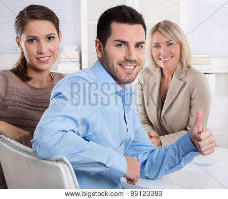 Young couple: adviser and customer talking together about finance. Business man making thumb up gesture for promotion.