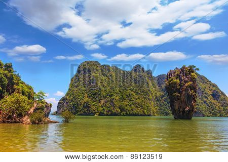 Calm bay and bizarre island. James Bond Island. The tourist season in Thailand