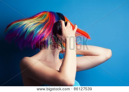 Beautiful Woman Wearing Colorful Wig And Headphones Against Blue Background