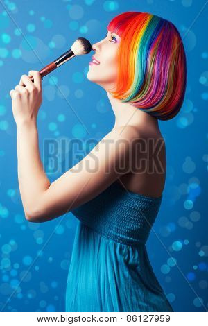 Beautiful Woman Wearing Colorful Wig And Holding Make-up Brush Against Blue Background