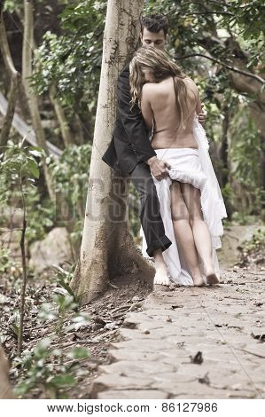 Young happy couple flirting outdoors along path in forest
