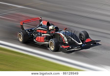 F1 Race Car Racing On A Track With Motion Blur