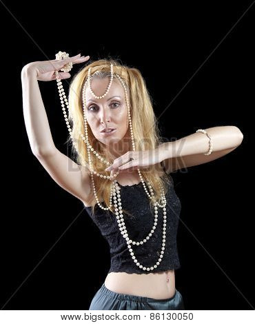 beautiful young blonde woman with long hair and a pearl beads on dark background.