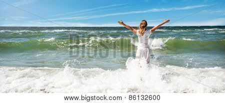 Woman in summer dress standing on a sea