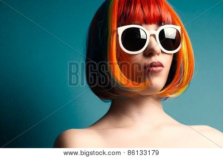 Beautiful Woman Wearing Colorful Wig And White Sunglasses Against Blue Background