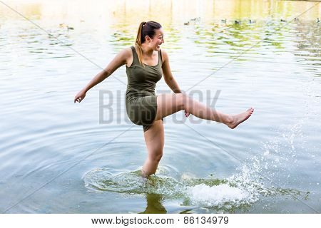 Young woman splashing at quarry pond with water having fun