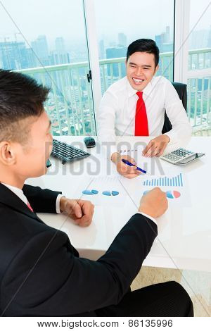 Asian banker offering client finance assets in bank office