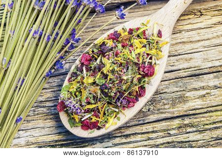 Natural dry herbal tea with meadow flowers near on a wood
