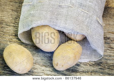 Potatoes in linen bag on the wooden table