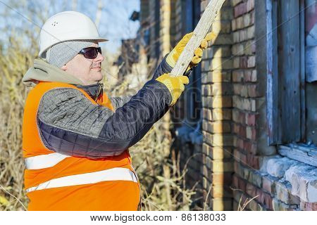 Construction worker with a wooden board near building