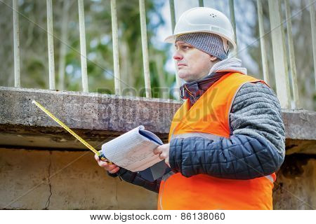 Engineer with tape measure and documentation under the bridge