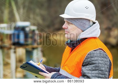 Engineer with documentation near power transformer