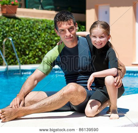 cute little girl with her father in a wetsuit near the pool