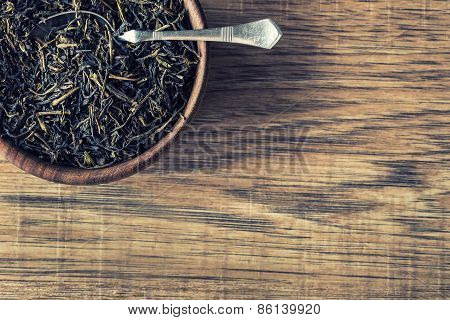 Dry tea in wooden plate on wooden table.