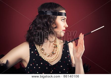 Beautiful Retro Woman Holding Mouthpiece Against Wine Red Background