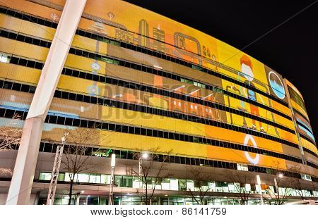 Iluminated Eliptical Building In Vivid Colors At Night