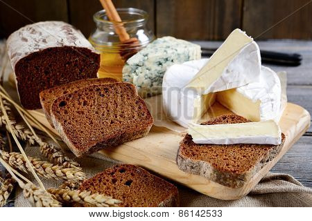 Brie Cheese, Black Bread Slices, Roquefort And Honey On A Board
