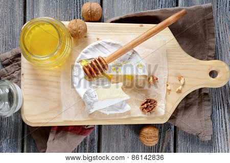 Brie Cheese With Honey And Walnuts On A Cutting Board